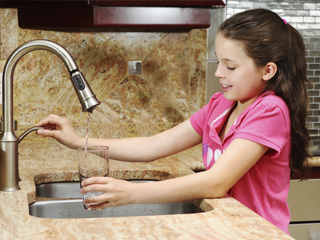 Girl using faucet to fill a glass of water