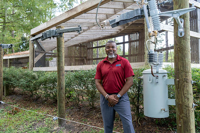 Gregg Sampson, OUC's Sr. Community Relations Coordinator, stands by small-scale utility poles with avian protection covers on powerlines.
